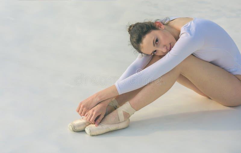 Jag behöver mer övning Den unga ballerina sitter på golv gullig dansare för balett Nätt kvinna i danskläder Övande konst av arkivbild