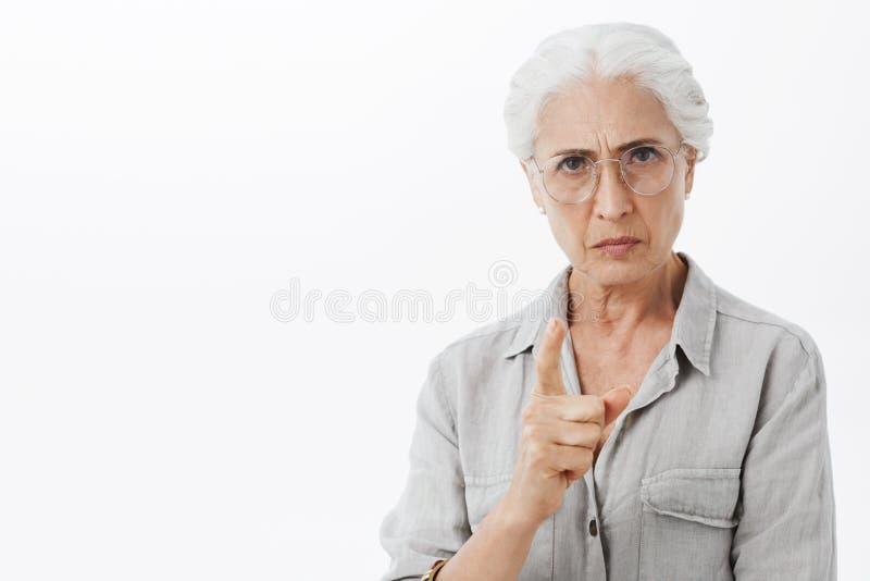 Jag förbjuder dig Stående av den strikta och allvarliga besvikna farmodern med vitt hår i exponeringsglas som rynkar pannan med t royaltyfri bild