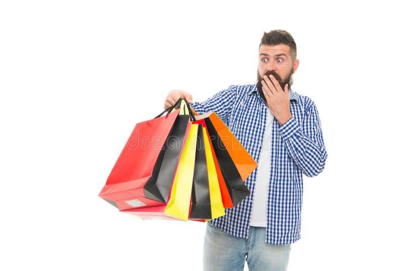Jag fortlevde Black Friday Den förvånade hipsteren som rymmer shoppingpåsar efter Black Friday, isolerade på vit sk?ggig man arkivbilder