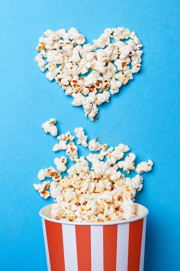 Jag gillar att hålla ögonen på filmer Spillt popcorn i formen av hjärta och pappers- hink i en röd remsa på blått royaltyfria foton