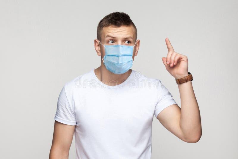 Jag har en aning Strålningskänslig ung man i vit skjorta med operationsmasken stående och försök komma ihåg hans idé arkivfoto