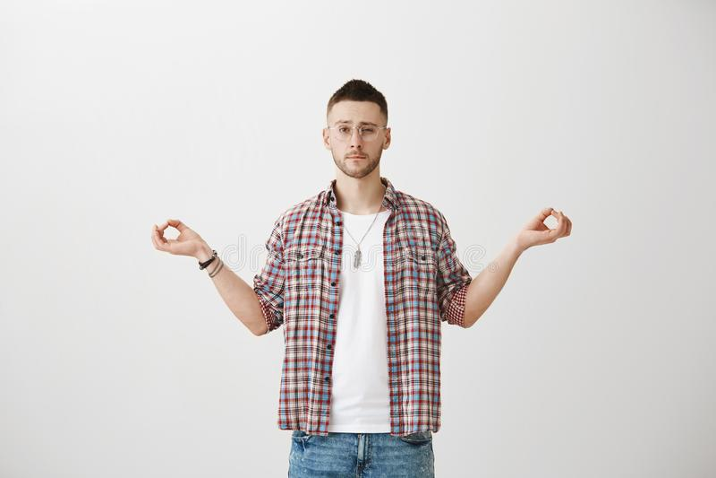 Jag kan inte koncentrera, medan du håller ögonen på Studioskott av det smarta snygga manliga anseendet med spridninghänder i medi arkivfoton