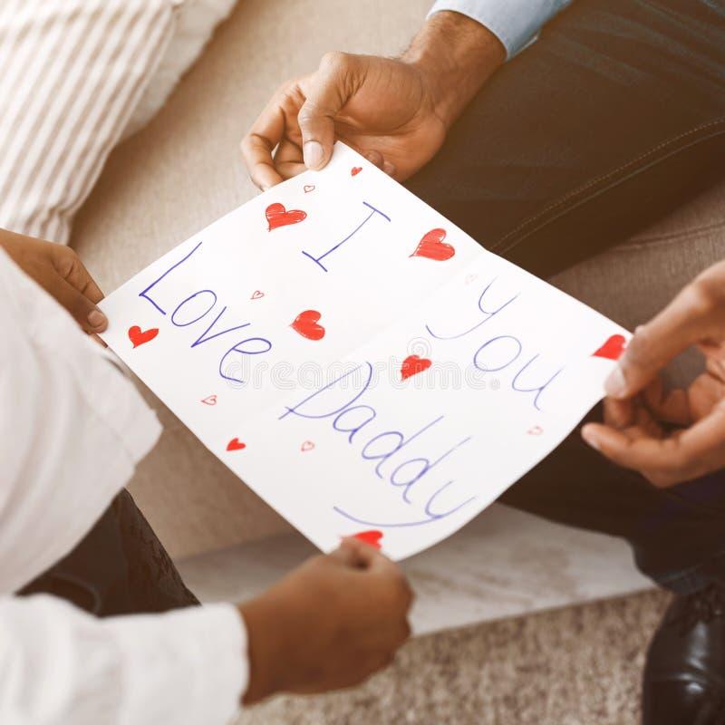 Jag ?lskar dig, pappa Liten flicka som ger vykortet för att avla royaltyfri fotografi