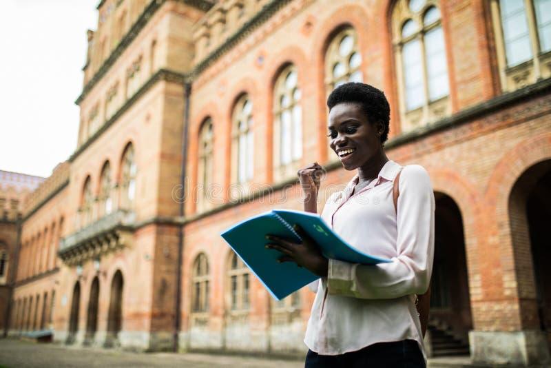 Jag passerar denna examen Läste lycklig stund för ung afro amerikansk studentblick anmärkningar från läroböcker, får punkter för  arkivfoto