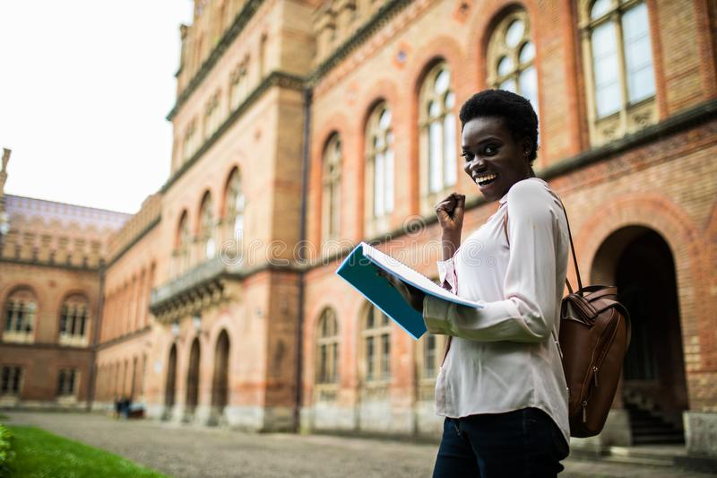 Jag passerar denna examen Läste lycklig stund för ung afro amerikansk studentblick anmärkningar från läroböcker, får punkter för  royaltyfria bilder