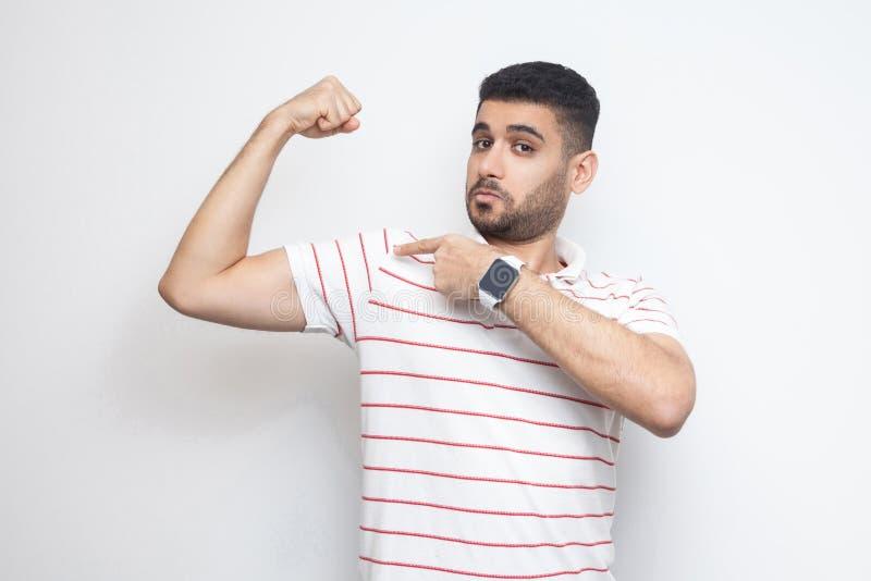 Jag ?r stark Stående av den stolta stiliga skäggiga unga mannen i randigt t-skjorta anseende som pekar på hans bicep och ser kame arkivfoto