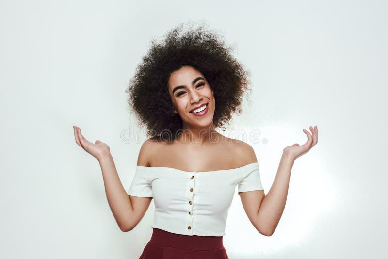 Jag vet inte, ledset! Stående av den nätta och attraktiva afro amerikanska kvinnan som ser kameran med och ler som fördelar royaltyfri fotografi