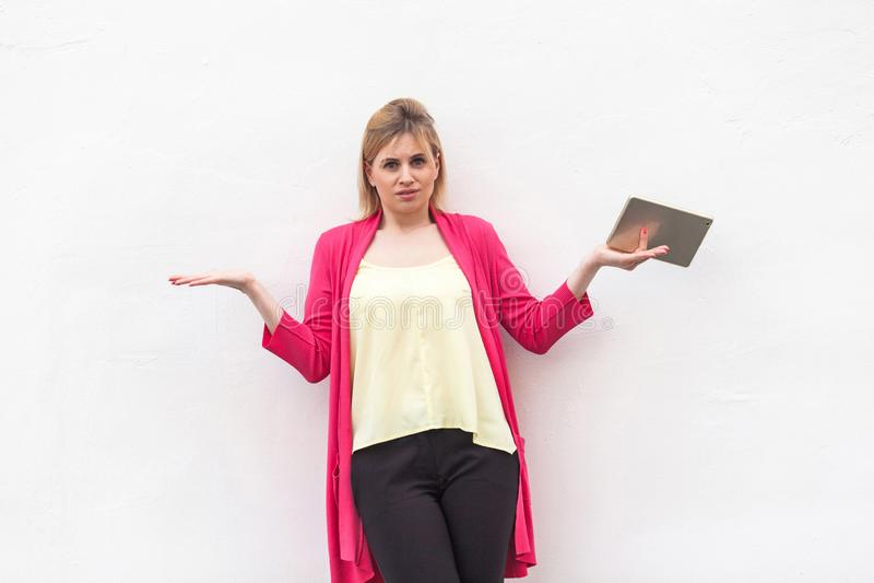 Jag vet inte! Stående av den skyldiga unga vuxna kvinnan i rosa blus och svarta flåsanden som står med lyftta armar och visar int royaltyfria bilder
