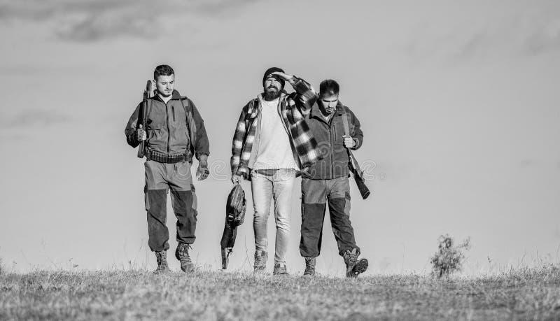 Jaga som hobby och fritid Jägare med vapen går solig nedgångdag Brutal hobby Grabbar som samlas för att jaga Gruppmän arkivfoton