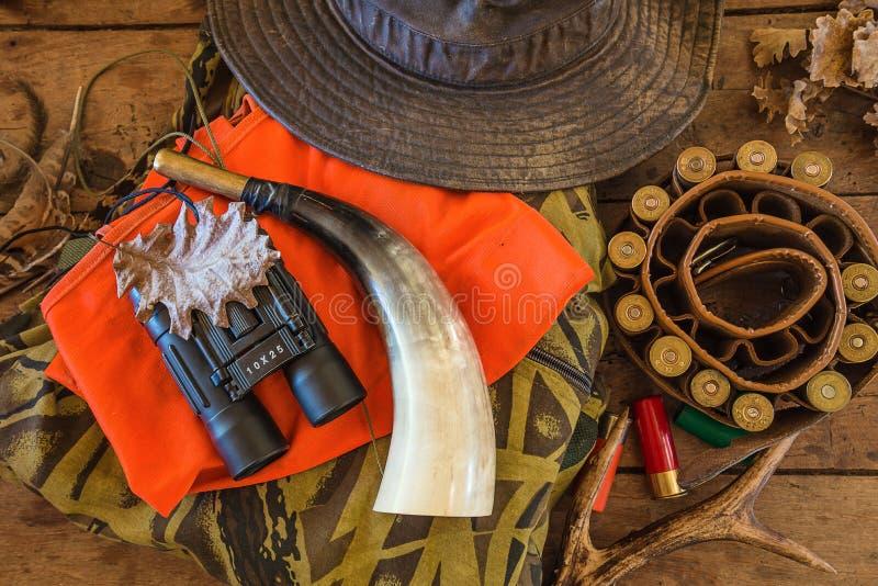 Jaga utrustningar på den bästa sikten för gammal träbakgrund Jaga bältet, hatt, kamouflage, orange waistcoat, muffar, hjorthorn p fotografering för bildbyråer