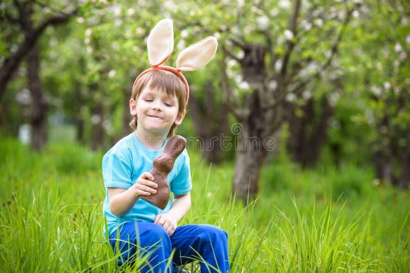 Jagd des kleinen Jungen für Garten Ostereies im Frühjahr am Tag nett stockbild