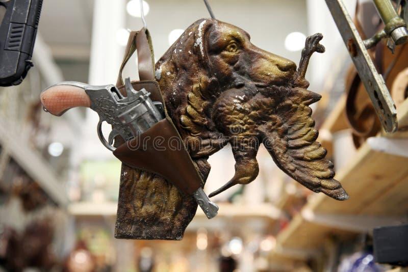 Jagdhund mit einer Troph?e in seinem Mund, in einem Eisenvogel und in einem Gewehr an einer Flohmarkt lizenzfreie stockfotografie