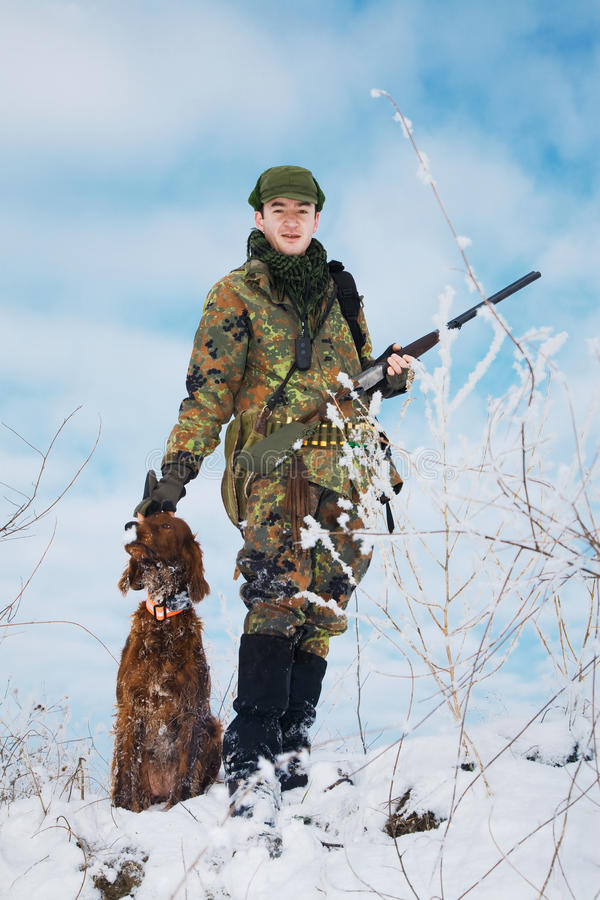 Jager die met zijn jachthond op de jacht wacht stock afbeeldingen