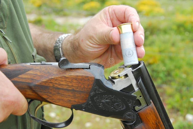 Jager die zijn wapen laadt stock afbeelding