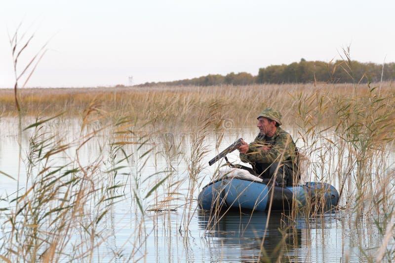 Jager in een boot stock foto