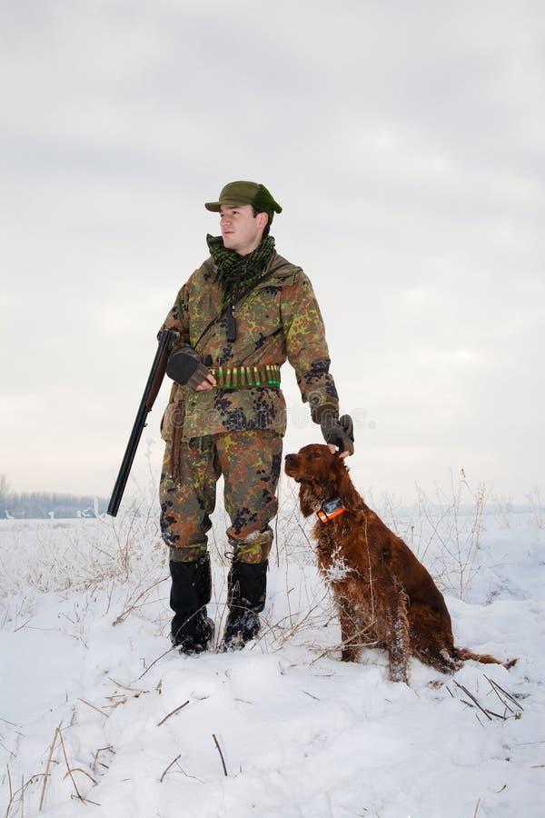Jager en zijn jachthond in de winter open seizoen stock afbeelding