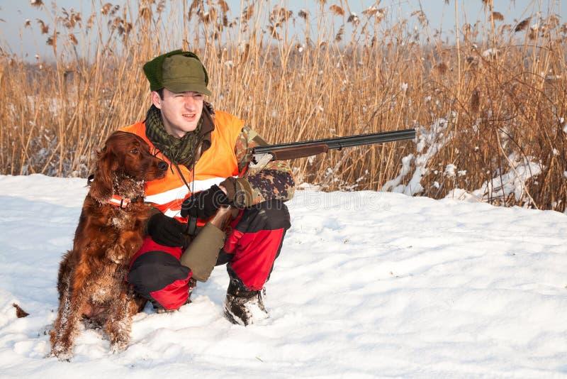 Jager en zijn jachthond in de winter open seizoen royalty-vrije stock fotografie