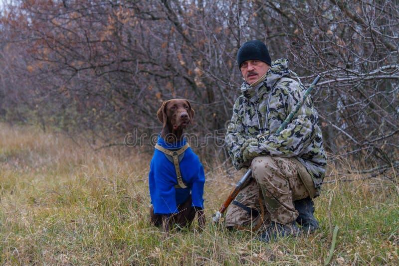 Jager met een hond genoemd Argo-kanon voor stock afbeeldingen