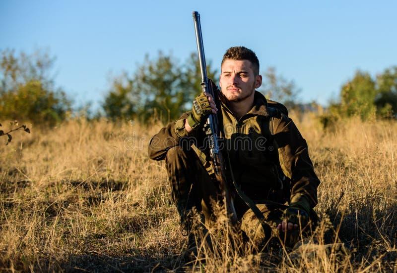 Jager tevreden met vangst het ontspannen Rust voor echt mensenconcept Jager met geweer het ontspannen in aardmilieu vermoeid royalty-vrije stock afbeelding