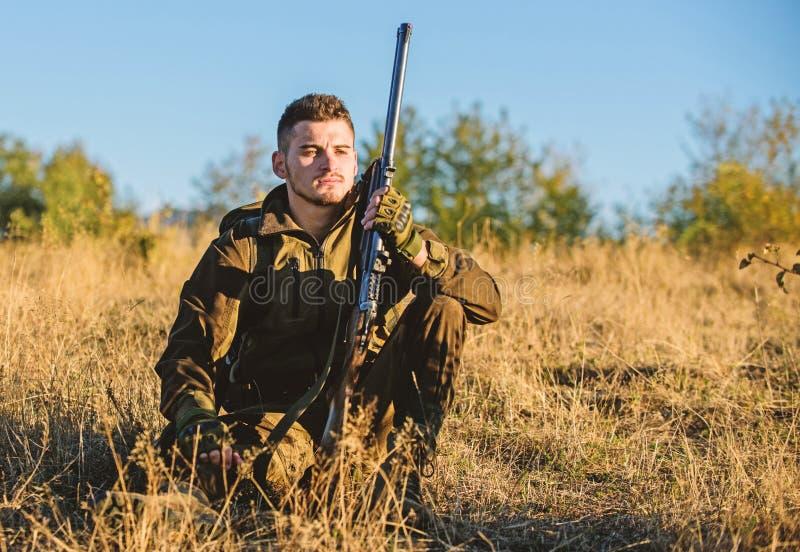 Jager tevreden met vangst het ontspannen Rust voor echt mensenconcept Jager met geweer het ontspannen in aardmilieu vermoeid stock afbeeldingen