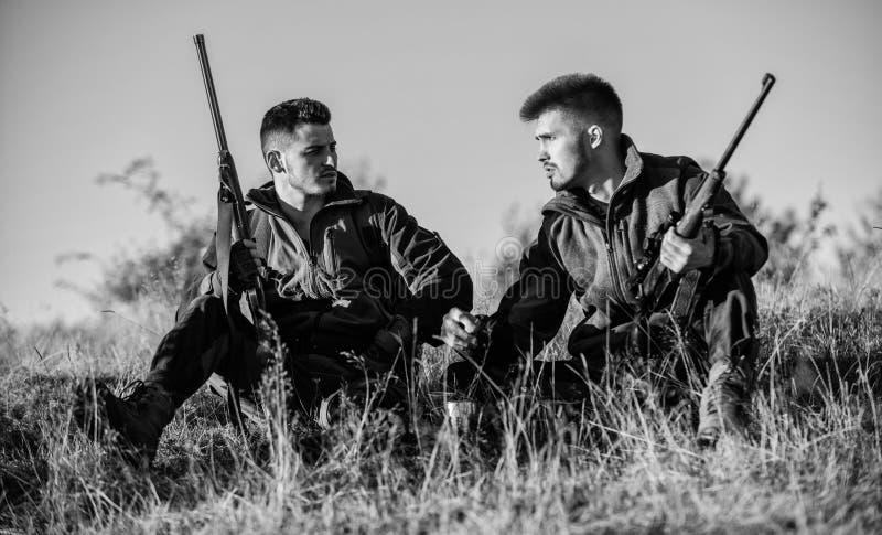 Jagers die met geweren in aardmilieu ontspannen De jacht met de vrije tijd van de vriendenhobby Jagers tevreden met vangst royalty-vrije stock foto