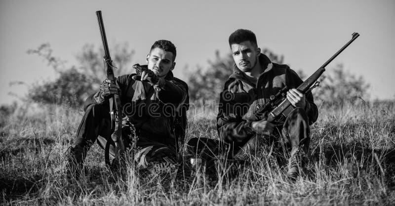 Jagers die met geweren in aardmilieu ontspannen De jagersvriend geniet van vrije tijd op gebied De jacht met vriendenhobby stock foto's
