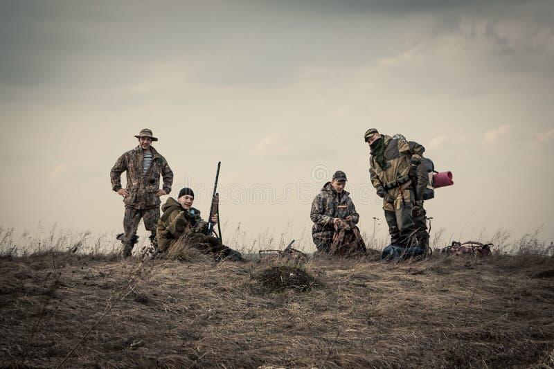 Jagers die zich tegen zonsonderganghemel op landelijk gebied tijdens jachtseizoen verenigen royalty-vrije stock afbeeldingen