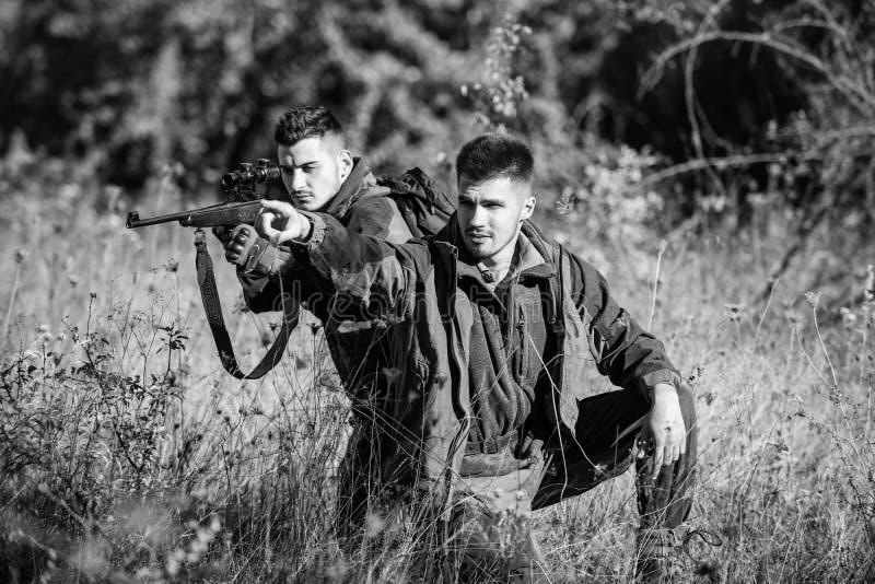 Jagers met geweren in aardmilieu De jagersvriend geniet van vrije tijd op gebied Jagersjachtopzieners die dier zoeken royalty-vrije stock fotografie