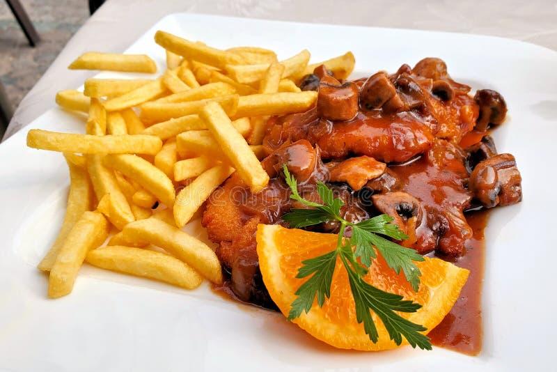 Jagerschnitzel alemán con una salsa y las patatas fritas, cierre de la seta para arriba en una placa blanca fotografía de archivo