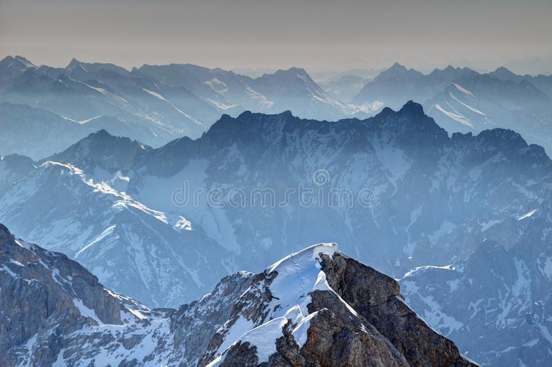 Jagged blue ridges of Wetterstein range from Zugspitze Germany. Jagged blue ridges of Jubilaumsgrat and Dreitorspitze in morning mist in snowy Wettersteingebirge stock images