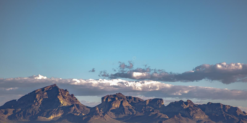 Jagged mountain beneath a cloudy blue sky stock photo