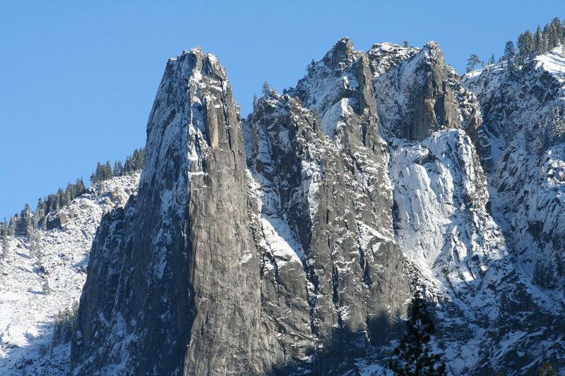 Jagged mountain peaks. Jagged snow covered mountain peaks with blue sky in background taken at Yosemite National Park in California stock photo