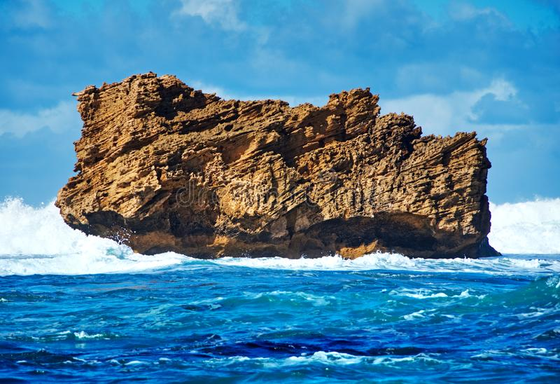 Jagged rock protruding from rough ocean water. Cloudy sky. Jaggy scraggy uneven swirling gnawed coarse royalty free stock photography