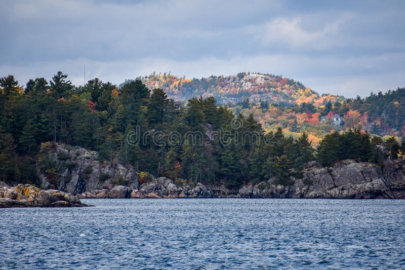 Stunning Fall Colors overlooking the mountains at Marquette, Michigan and Lake Superior. Jagged rocks coming out of Lake Superior a with Sugarloaf mountain and royalty free stock photos