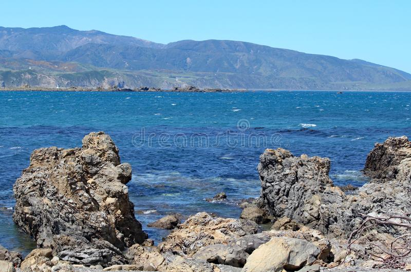 Jagged rocks on the edge of Lyall Bay in Wellington, New Zealand.  stock photo