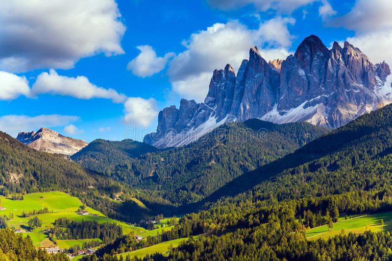 The jagged rocks. Wall of jagged rocks and grassy slope of the mountain. Rural pastoral in the Val de Funes, Dolomites. The concept of ecological tourism royalty free stock images