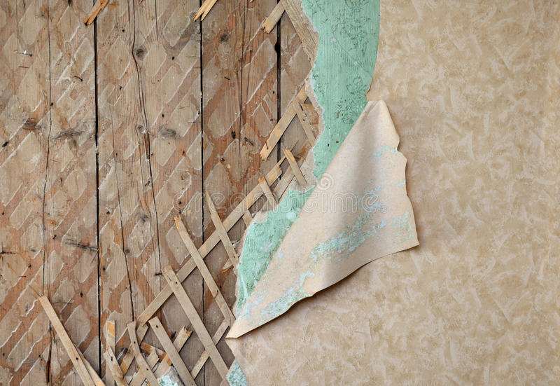 Jagged wallpaper on old destroyed wall. Fragment of old destroyed wall with jagged wallpaper and lath in abandoned house royalty free stock image