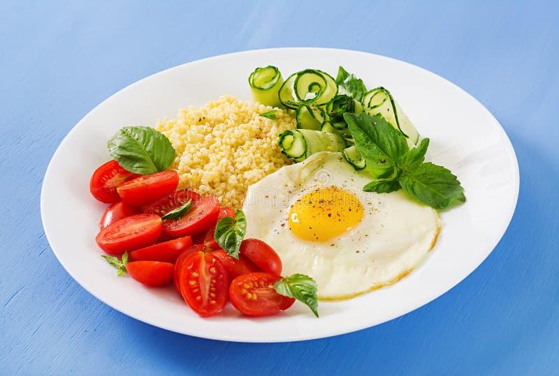Jaglana owsianka, pomidor i ogórkowi jajka, sałatkowi i smażący zdjęcie royalty free