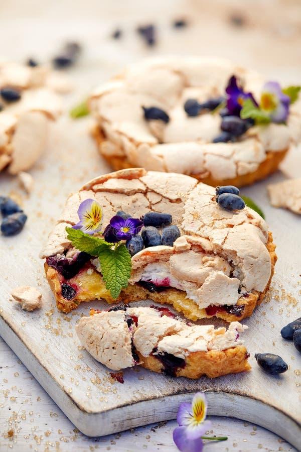 Jagodowy beza tort z jadalnymi kwiatami, wyśmienicie deser fotografia stock