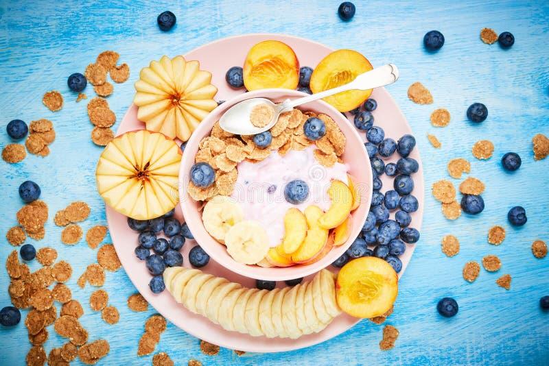 Jagodowy grecki jogurt z czarnymi jagodami, bananem i płatkami w różowym pucharze na błękitnym drewnianym stole frefh, obraz stock