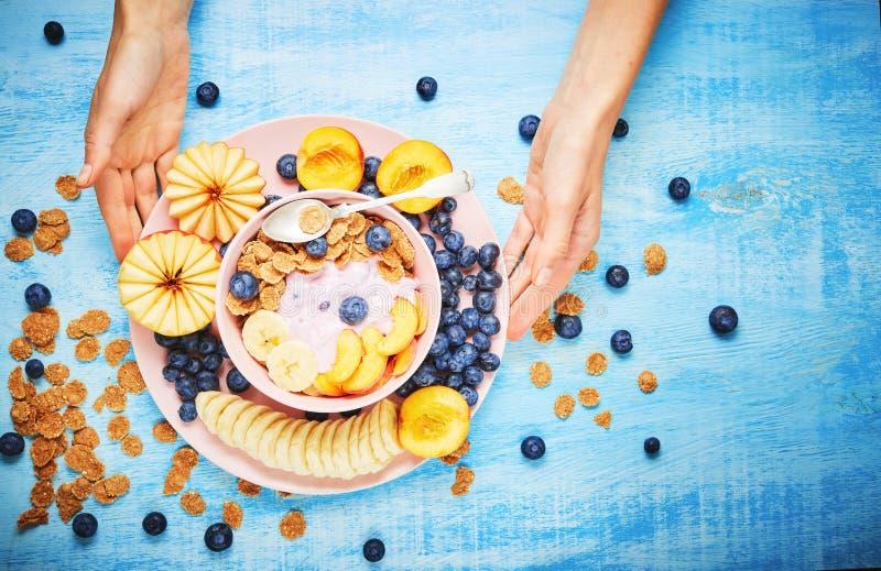 Jagodowy grecki jogurt z czarnymi jagodami, bananem i p?atkami w r??owym pucharze na b??kitnym drewnianym stole frefh, zdjęcie stock