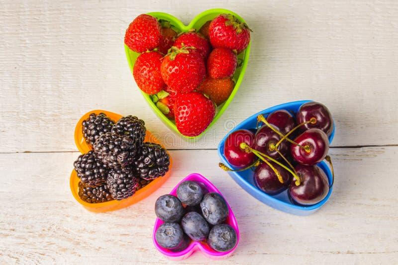 Jagody, truskawki, czernicy wiśnie i czarne jagody w sercowatym talerzu na białym drewnianym starym stołowym zakończeniu, jesieni zdjęcie royalty free