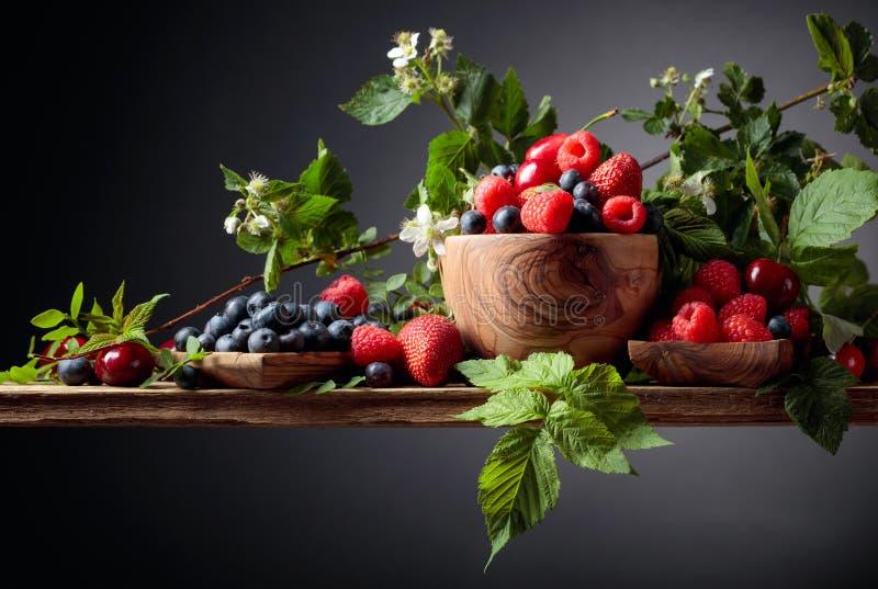 Jagody zbliżenia kolorowa asortowana mieszanka truskawka, czarna jagoda, malinka i słodka wiśnia na starym drewnianym stole, obraz royalty free