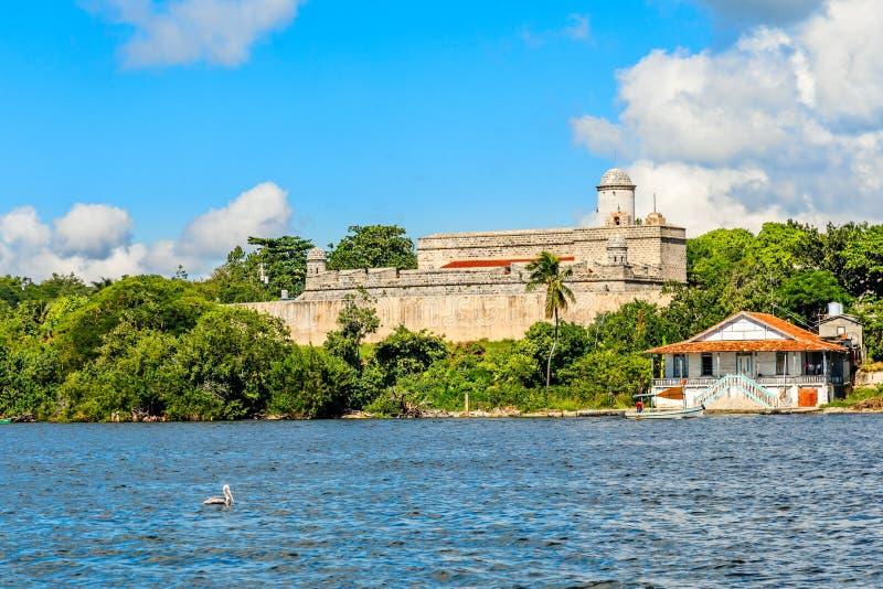 Jagua roszuje warowne ?ciany z drzewami i ?odziami rybackimi w przedpolu, Cienfuegos prowincja, Kuba fotografia royalty free