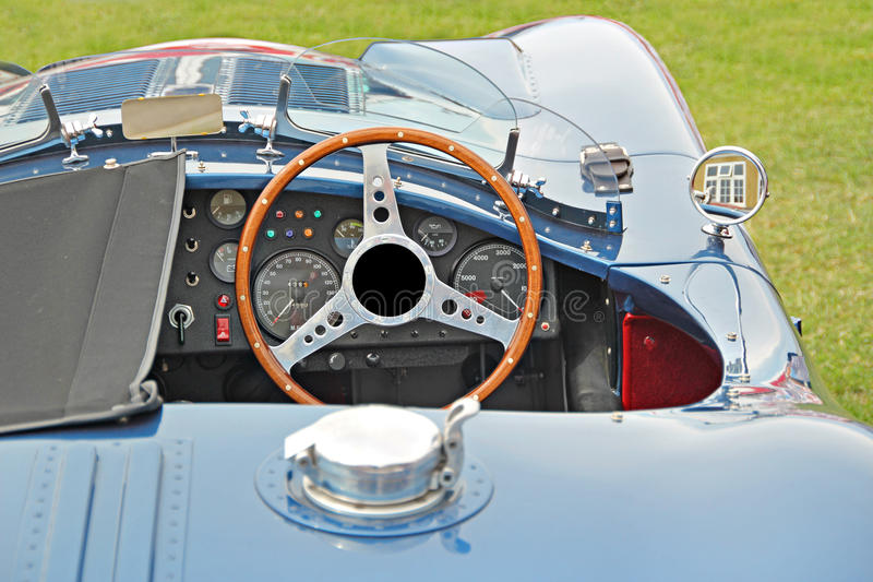 Jaguar racing sports car. Photo of a jaguar racing sports car showing cockpit with wooden steering wheel and instrument panel stock image