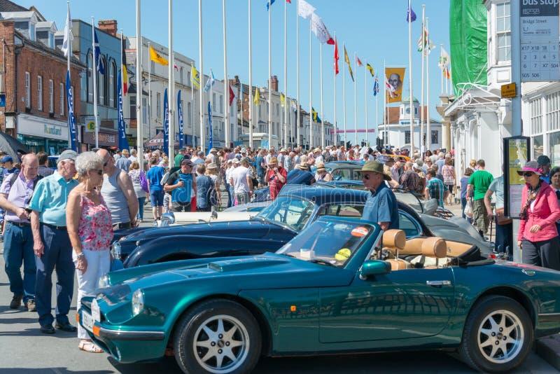 Jaguar XJS rodeado por la gente y las astas de bandera internacionales en la demostración de coche clásica fotografía de archivo