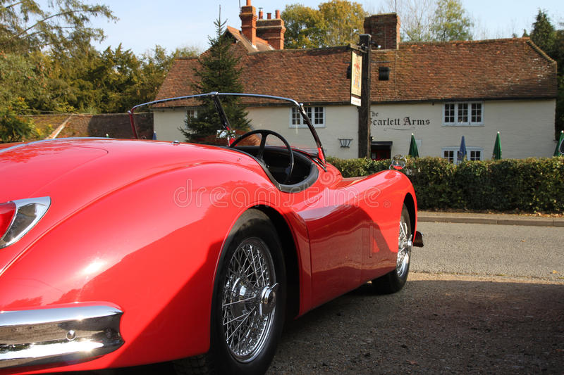 Jaguar XK120 outside the Scarlett Arms public house in Surrey. England. Red open top vintage Jaguar XK120 with wire wheels stock photo