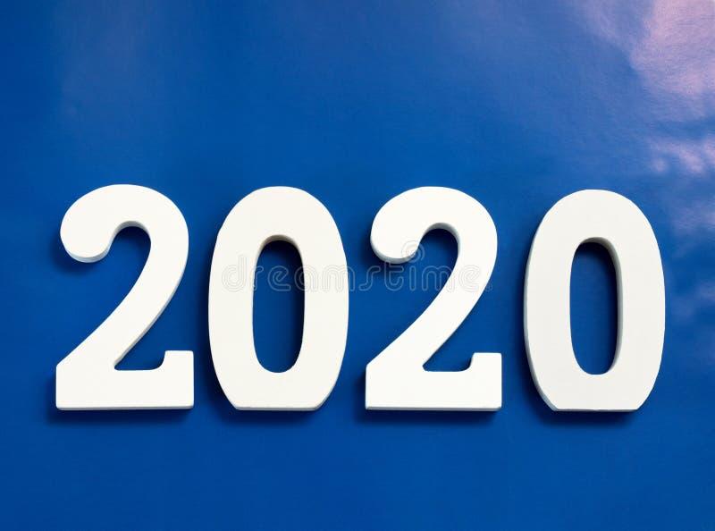 Jahr 2020 gemacht von den hölzernen weißen Zahlen auf einem blauen Hintergrund lizenzfreie stockbilder
