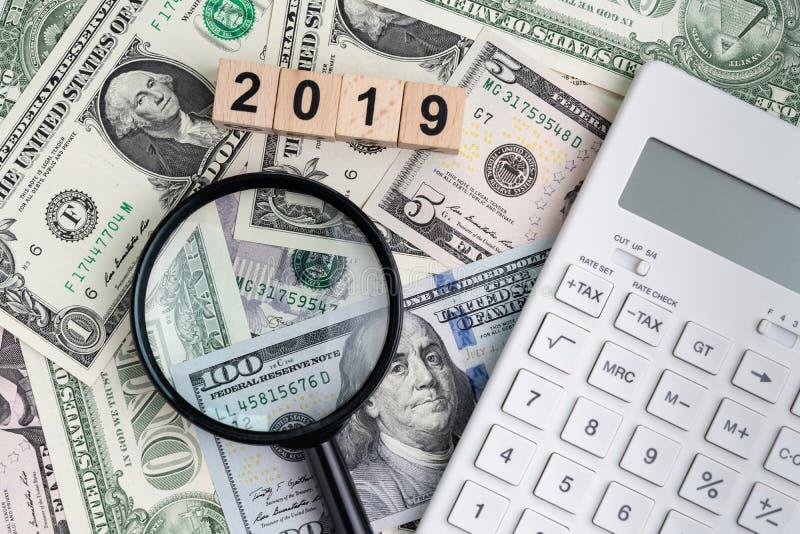 Jahr 2019 suchend nach Finanzerfolg oder Gewinn- oder Steuerberechnungskonzept, schwarze Lupe finden mit dem Würfel hölzern stockfoto