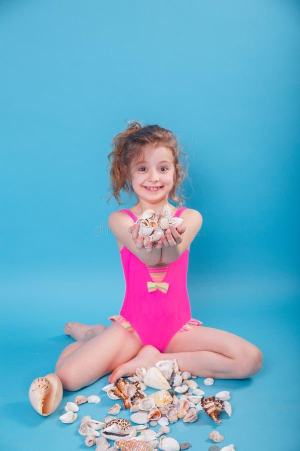 7 Jahre alte Kinderholding-Muschel auf blauem Hintergrund Fokus auf Muschel stockbilder